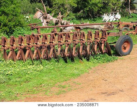 Old Rustic, Metal Farm Equipment, Surrounded By Grass And Other Vegetation