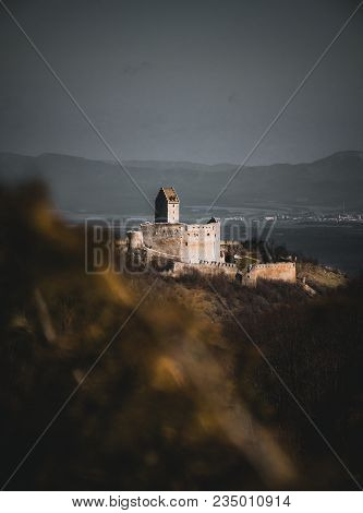 Photo Through The Bluerred Yellow Leafs Of Illuminated Castle With Wall On Right Side In Slovakia -