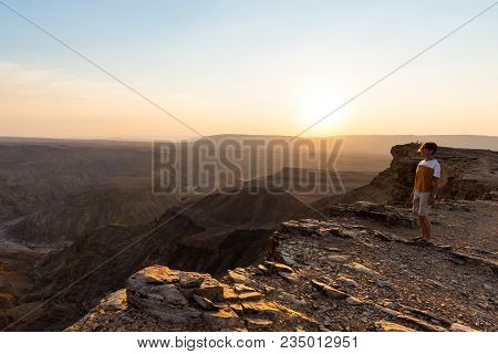 One Person Looking At The Fish River Canyon, Scenic Travel Destination In Southern Namibia. Expansiv