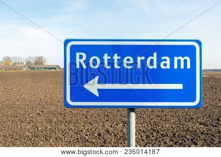Large Reflective Blue Sign With A White Arrow In The Direction Of Rotterdam. The Traffic Sign Is Pla