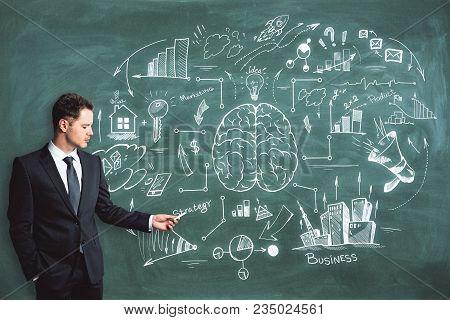 Handsome Caucasian Businessman Drawing Business Brain Sketch On Chalkboard Background. Brainstorm, E