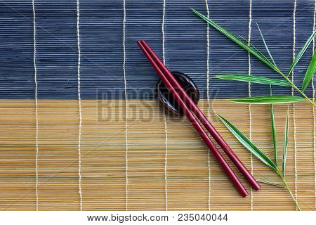 Red Chopsticks With Holder And Bamboo Leaves On Bamboo Mat, Top View Or Flat Lay Design