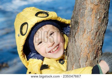 Boy Portrait In Coat Looking From Tree. Happy Smiling Kid. Schoolboy Child 7 Years