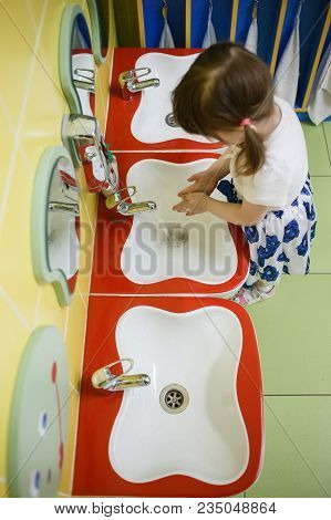 Child Girl Washing Hands In A White Basin With A Bar Of White Soap.