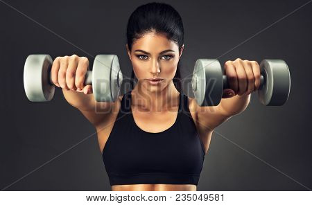 Beautiful Fitness Woman With  Lifting Dumbbells . Sporty Girl Showing Her Well Trained Body .  Well-