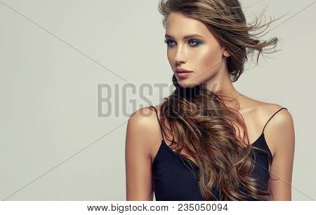 Girl With Long Brown And   Shiny Curly    Hair .  Beautiful  Brunette Model Woman In A Black Topic W