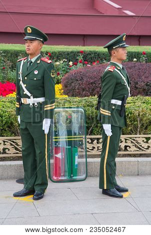 BEIJING, CHINA - OCTOBER 13, 2017: Unidentified men, police guards in front of the Forbidden City (Palace museum), the Chinese imperial palace.