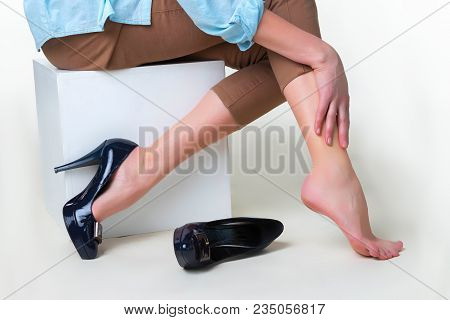 Cropped Image Of Woman In High Heels Massaging Her Tired Legs. Varicose Veins Concept. Painful Varic