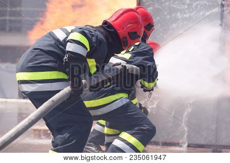Firefighters In Action Spraying Fire With Fire Hose. Fire Department Training.