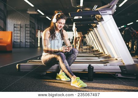 Beautiful Young Caucasian Girl Sportswoman Sitting, Resting After Training On Treadmill Against The