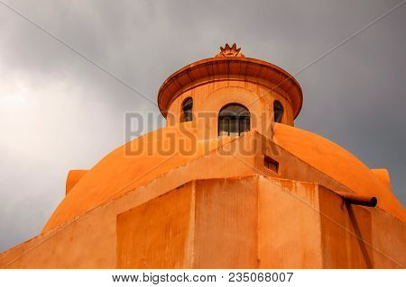 Exterior Of Ocher Church Dome In Mexico Against A Stormy Sky