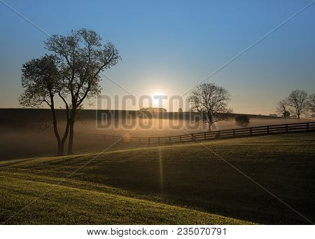 Sun Rises Over Foggy Hills Of Kentucky With Black Fence Running Through
