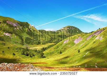 Mountain Landscape With Green Hills, Blue Sky And Herd Of Grazing Cows In Valsabbia, Brescia, Italy.