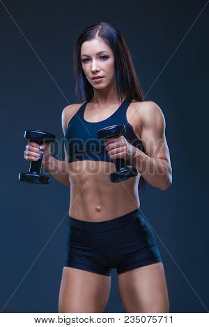 Brutal Athletic Sexy Woman Pumping Up Muscules With Dumbbells. The Concept Of Exercise Sports, Adver