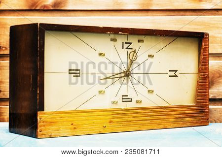 Old Rectangular Clock On The Background Of Wooden Wall. The Clock Is Decorated With Wood.