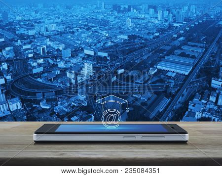 E-learning Icon On Modern Smart Phone Screen On Wooden Table Over City Tower, Street And Expressway,