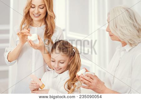Like Mother Like Daughter. Unearthly Beautiful Ladies Of Different Age Applying Creams While Spendin