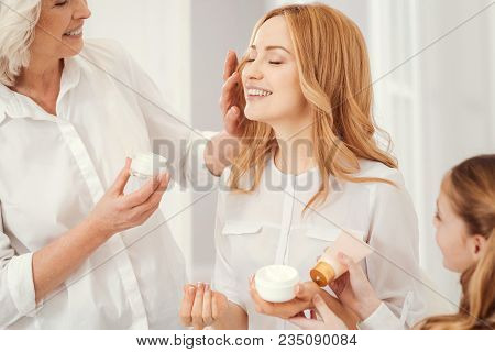 Joyful Moment. Radiant Mature Blonde Lady Sitting On A Chair And Beaming While Enjoying The Time Spe