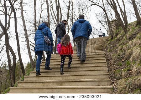 Several People Climb Up The Stone Stairs In The Park