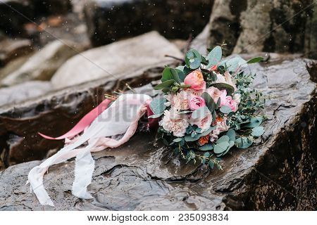 Wedding Bouquet Of Peonies With Ribbons On Stone