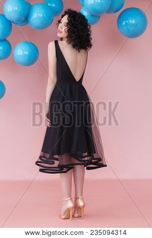 Studio Portrait Of Brunette Girl Posing In A Luxurious Cocktail Dress -back Full Body In Pink Studio