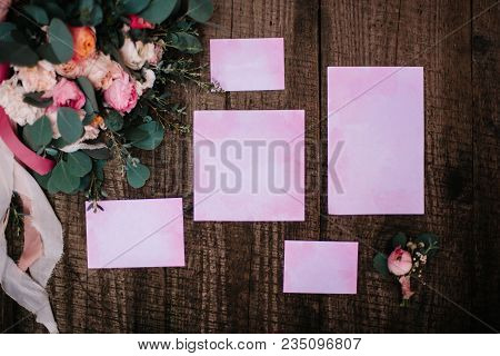 Wedding Decor With A Rose And Invitations, On A Wooden Background