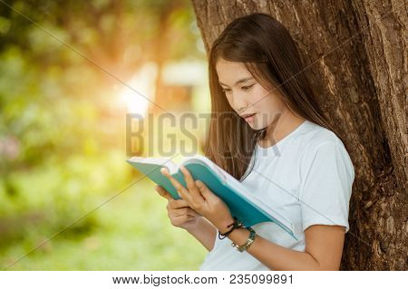 Asian Girl Reading Book At Park In Summer Sunset Light. Asian Woman Reading Book In Thailand. Asian
