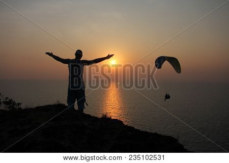 A Man At Sunset, Standing On A Cliff Or At The Top Of A Mountain, Looking At The Sun And Dreaming Of