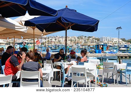 Marsaxlokk, Malta - April 1, 2017 - Tourists Relaxing At A Pavement Cafes Along The Waterfront With