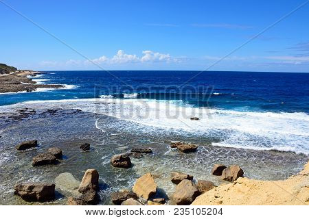 View Along The Coastline With Rocks In Shallow Water In The Foreground, Redoubt, Marsalforn, Gozo, M