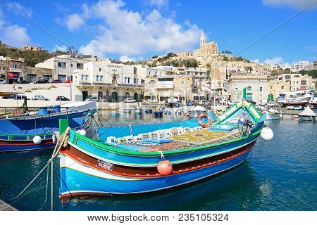 Mgarr, Gozo, Malta - April 3, 2017 - Traditional Fishing Boats In The Harbour With The Our Lady Of L