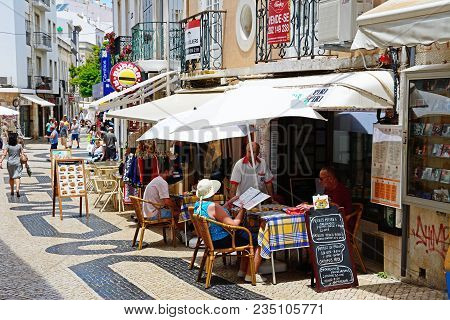 Lagos, Portugal - June 9, 2017 - Tourists Relaxing At Pavement Cafes Along R Lima Leitao In The Old