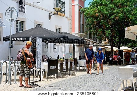 Lagos, Portugal - June 9, 2017 - Street Performer Singing And Playing His Guitar Along R 25 De Abril