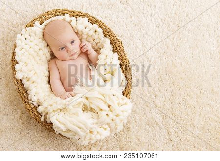 Newborn Baby, Beautiful New Born Kid One Month Old In Basket With Woolen Blanket Over Carpet Backgro