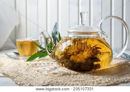Exotic Green Tea With Flowers In Glass Teapot And Tea Cup