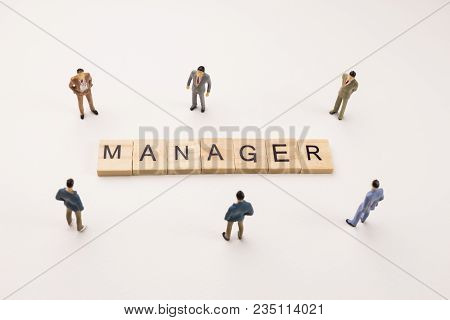 Miniature Figures Businessman : Meeting On Manager Letters By Wooden Block Word On White Paper Backg