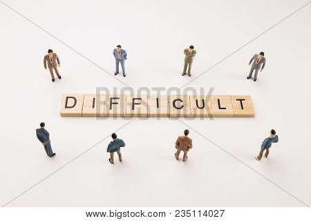 Miniature Figures Businessman : Meeting On Difficult Letters By Wooden Block Word On White Paper Bac