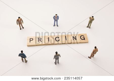 Miniature Figures Businessman : Meeting On Pricing Letters By Wooden Block Word On White Paper Backg