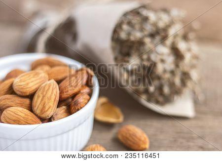 Almonds In A White Ceramic Bowl On The Wooden Table. Almonds Are Rich In Nutrients, Vitamins And Min