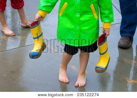 Feet Of A Young Boy, His Sister, And His Dad After Walking In The Rain And Mud.  The Boy Is Now Bare
