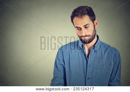 Lack Of Confidence. Shy Young Handsome Man Feels Awkward Isolated On Grey Wall Background. Human Emo