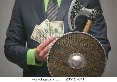 Businessman Holds In Hand A Toy Viking Axe Weapon And Shield. Life Or Finance Insurance Agent. Money