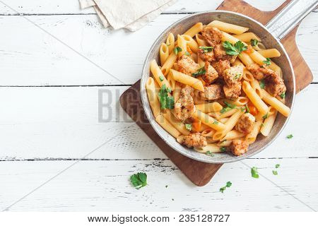 Penne Pasta In Tomato Sauce With Chicken,  Parsley In Pan. Chicken Italian Penne Pasta Over White Ba