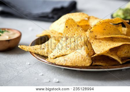 Nachos Chips And Assorted Dip Sauces. Tortilla Corn Nachos Chips With Salsa, Melted Cheese And Guaca