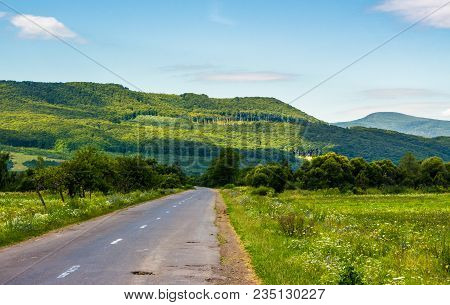 Road Through Mountainous Countryside. Fields And Forest On The Side.