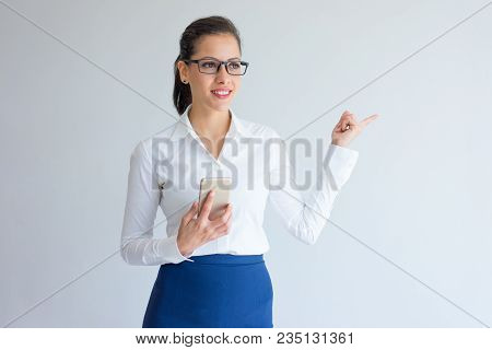 Cheerful Pensive Young Businesswoman Pointing Aside. Smiling Thoughtful Caucasian Female Company Emp