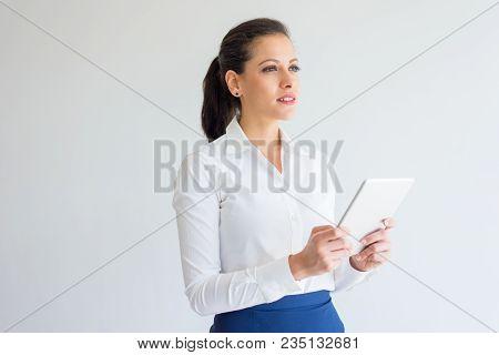 Pensive Ambitious Young Businesswoman Using Modern Device. Thoughtful Purposeful Caucasian Business
