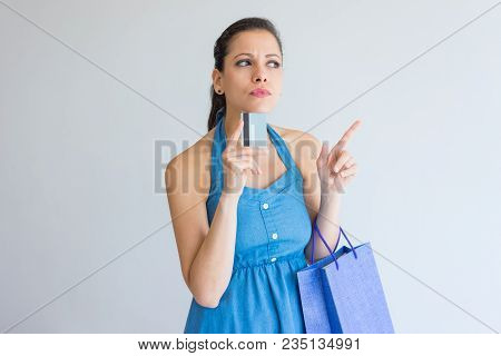Pensive Concentrated Shopaholic Leaning On Credit Card And Pointing Aside. Serious Frowning Young Wo
