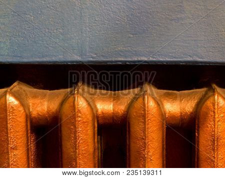 Copper Heating Radiator With Blue Wall Background