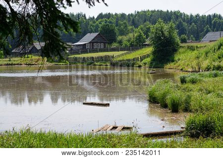 The Village Pond. Russian Village On The Shore Of The Pond. Russia, The Urals. Summer, July